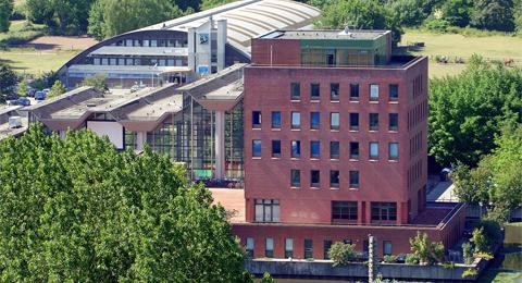 Das Bild zeigt das Institut für Sportwissenschaft im Sportzentrum an der Olshausenstraße, im Hintergrund (mit dem gebogenen Dach) ist das Fitness-Zentrum